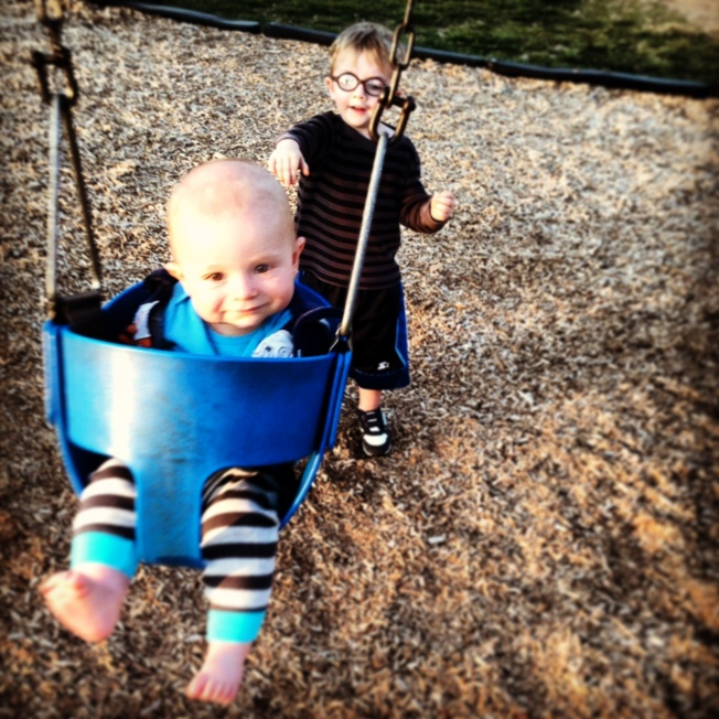 Nolan pushing Micah on swing